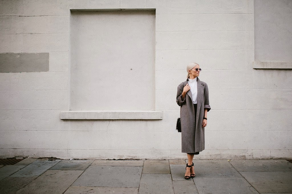 charleston street style winter 2015 in style trend high neck sleeveless white top shirt asos leather midi skirt calf length grey oversized duster coat long menswear ashley olsen style guide platinum blonde model middle part hair round sunglasses black quilted bag steve madden marlenee ankle strap heels onyx nail polish butter london euro daniel wellington sheffield lady black and rose gold watch sc fashion blogger dannon k collard