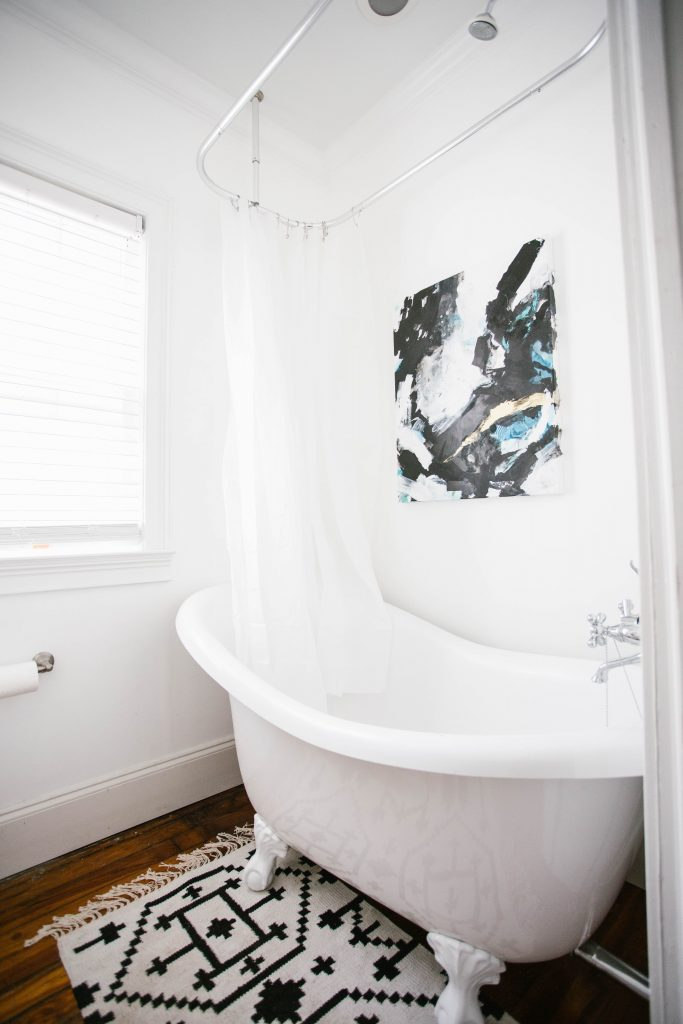 Guest Bathroom Reveal Modern Historic Downtown Charleston Home Renovation   // Charleston Fashion Blogger Dannon Like The Yogurt    Urban Outfitters black hexagon hand towel ring DIY cedar and moss brass sconce white clawfoot tub shower round brass vanity mirror target cement planter hex white vase white walls marble cararra countertops black and white geometric kilum rug nate burkus